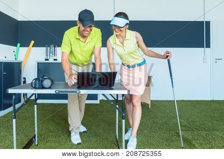 Cheerful young woman analyzing and watching on laptop her video recorded strike during a contemporary golf class with an experienced instructor