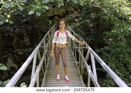 young girl stands on bridge over river Agura, Sochi, Krasnodar Territory