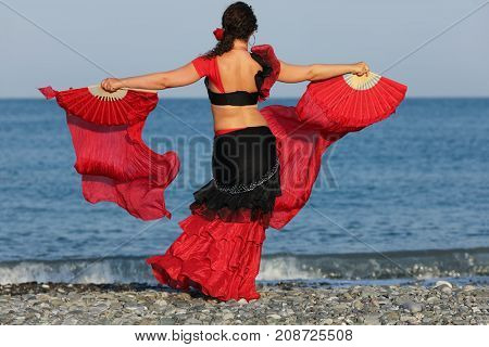 Dancer woman in black and red suit with fan dancing on seashore, back view