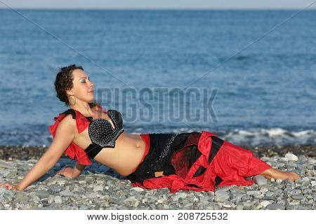 beautiful dancer woman in black and red suit lays by seashore