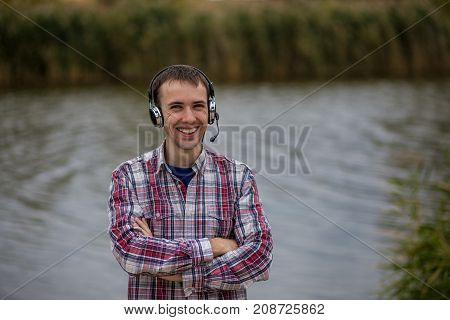 Portrait of a handsome smiling customer service operator wearing a headset standing on river pier