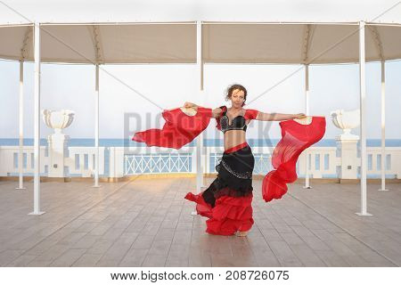 beautiful dancer woman in black and red suit with fan dancing on seashore