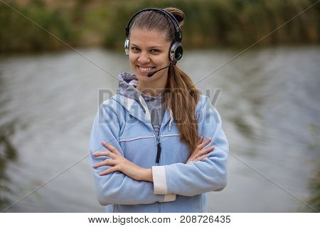 Portrait of a pretty smiling customer service operator wearing a headset standing on river pier