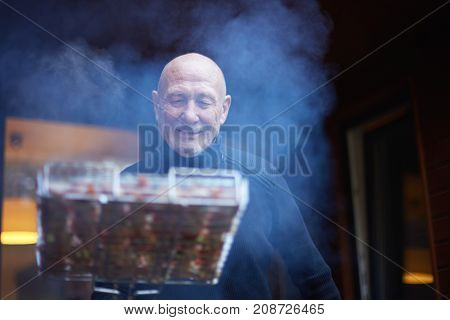 Close up portrait of handsome Caucasian man cooking steak on barbecue grill outdoors. Attractive senior man with grey hair dressed casual preparing dinner for his family at a barbecue party.