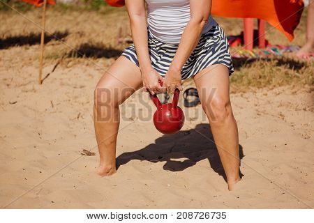 Detail of woman doing exercises on the beach in functional training circuit