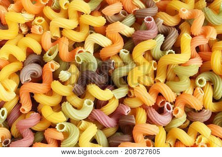 Food background - uncooked colorful Cavatappi (Celentani) durum wheat pasta with beetroot, spinach and tomato