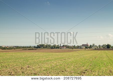Crop land landscape field with small Village on the Horizon