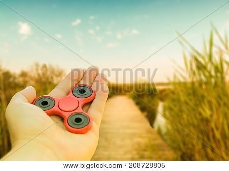 Fidget spinner in hand lake and sky background