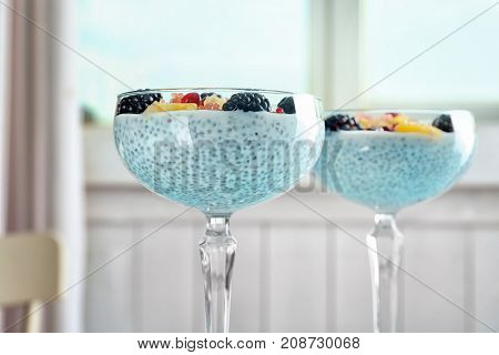Glasses with delicious chia seed pudding on blurred background, close up