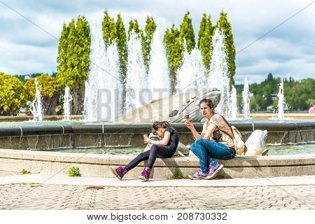 Saguenay Canada - June 3 2017: People mother and daughter sitting by whale fountain in downtown city park in Quebec eating licking ice cream during hot summer day