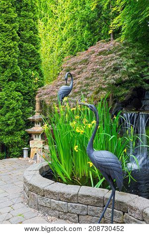 Japanese inspired backyard home garden with bronze cranes stone pagoda water fountain pond bamboo and maple trees