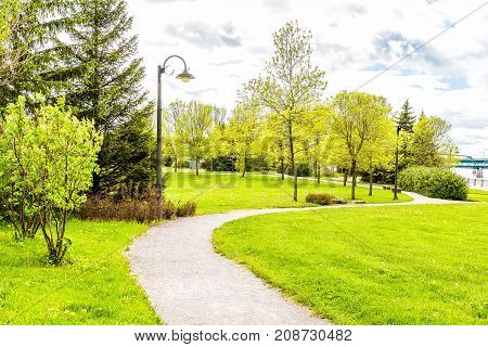 Sidewalk in green downtown city park in Saguenay Canada Quebec during summer with fjord river bridge boardwalk promenade