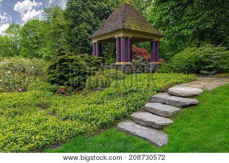 Rock stone stair steps leading up to gazebo in backyard garden