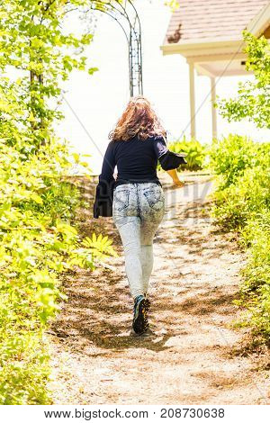Back Of One Young Woman Running Up Hill In Sunny Bright Golden Woods Forest In Quebec, Canada