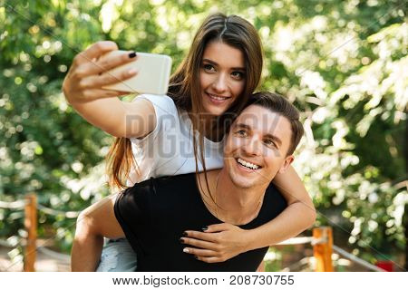 Portrait of a smiling attractive couple in love making selfie at the park, piggyback ride