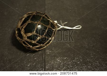 Glass float in net with wet tiles underneath