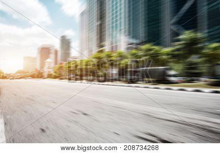 blurry empty asphalt road and modern buildings in midtown of kuala lumpur