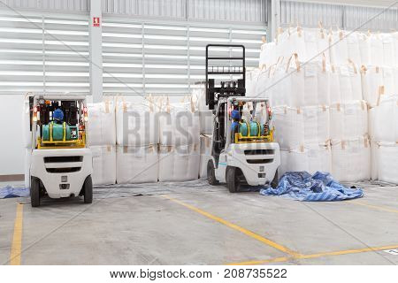 Warehousing. Forklift driver stacking big bag of raw material in warehouse.
