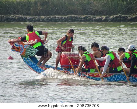 Taipei Taiwan, 20 June 2015: Closeup view of boat head with drum, drummer and people paddling at Dragon boat festival race on tamsui river in Taipei