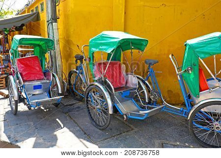 Hoian, Vietnam.  Old town with Colourful Pedicabs waiting for Tourists.