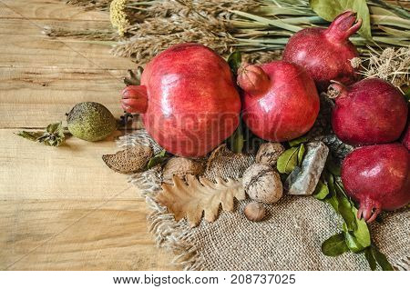 Ripe pomegranate fruit with nuts and dry bouquet of wild flowers on the rough unpainted boards