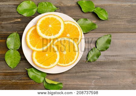 Slices of Navel orange fruit on white dish and wooden background.Top view