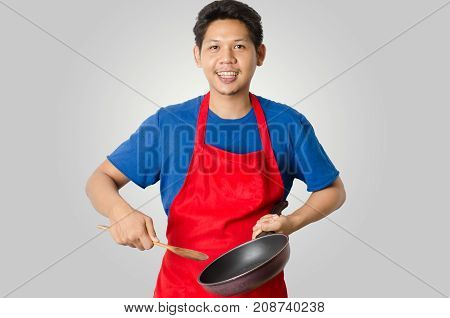 Asian man wear red apron and holding pan and ladle for cooking isolated on gray background