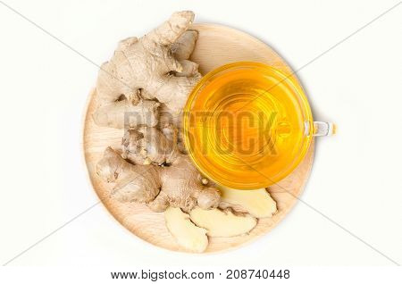 Cup of ginger tea with fresh ginger on wooden dish isolated on white background, herbal drink