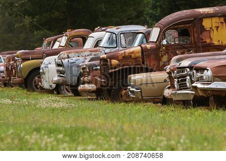 Gainesville GA USA - June 1 2017: A row of old discarded cars and trucks sit lined up all in a row in a grassy junkyard field on June 1 2017 in Gainesville GA.