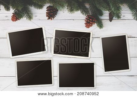 Christmas background - Blank photo frame paper with fir leaves and pine cones decorating rustic elements on white wood table. Creative Flat layout and top view composition.
