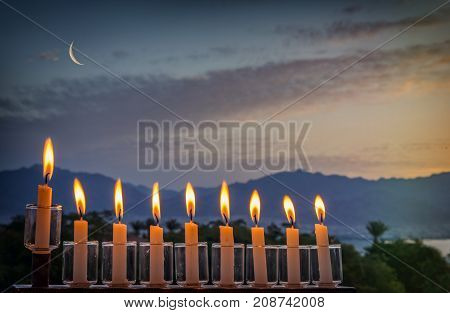Low key image with menorah with glitter lights of burning candles and crescent moon on black sky. Image symbolizes Jewish holiday of Hanukkah