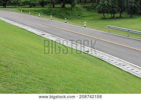 Asphalt Road along hillside green grass. The country road through the hills ..