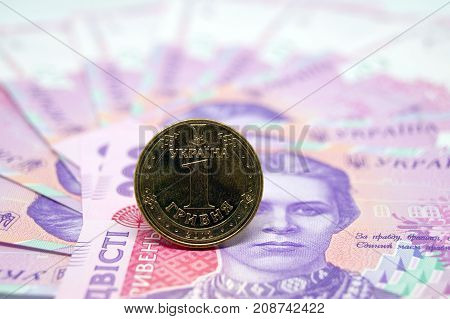 The coin is one hryvnia against the background of paper banknotes of the Ukrainian currency. Ukraininan money.