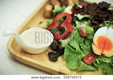 Caesar salad with croutons, boiled eggs, cherry tomatoes and fried crispy bacon on top.