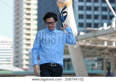 Frustrated stressed young Asian businessman walking and throwing his necktie in urban building city background.