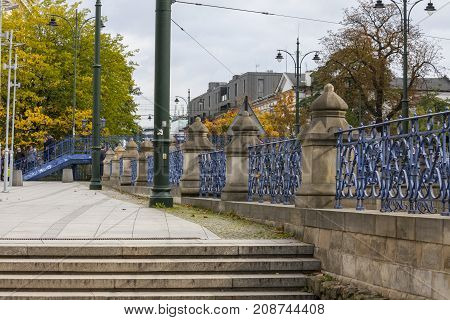 Blue fence and footbridge over tram tracks Cracow Poland - October 13 2017: Intensive blue fence and entry to footbridge over tram tracks near Galeria Krakowska shopping centre square Cracow Poland.