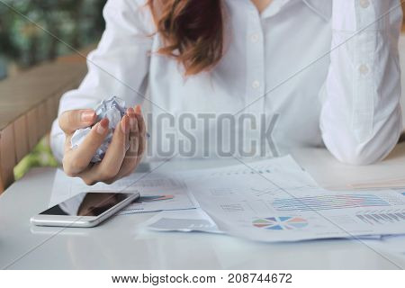 Vintage image tone of hands of businesswoman holding crumpled paper on the desk in office. Frustrated stress business concept.
