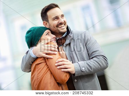 Smiling couple in love outdoors.Young happy couple hugging on the city street.