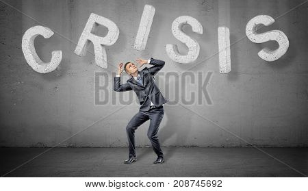 A businessman cowers under large concrete letters making up a word Crisis above him. Problems and solutions. Difficulties. Business troubles.