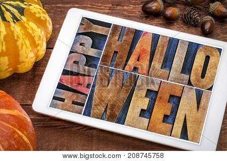 Happy Halloween greeting card -  text in vintage grunge wood type printing blocks on a digital tablet with a pumpkin and squash
