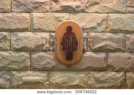 Sign of female toilet figure on textured marble wall