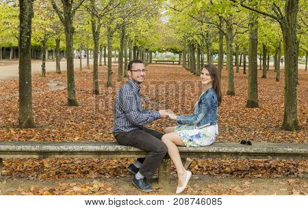 Lovely couple having fun together on a stone bench in a park in autumn.