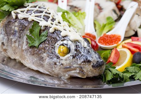 Seabass head with caviar and vegetables on plate