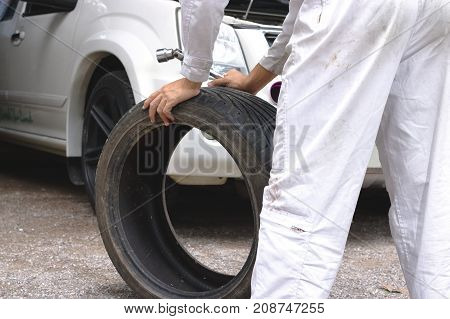 Hands of mechanic in white uniform holding tire at the repair garage background. Car service concept.
