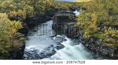 Soft rapids in a river, surrounded of cliffs, rocks. Some sunshine. Colorful forest both sides.