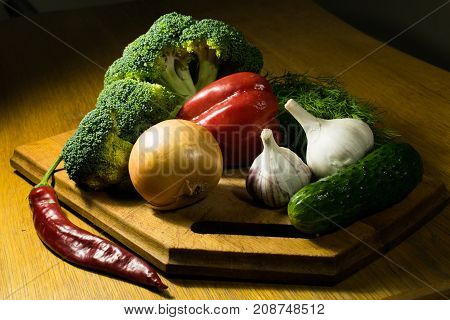 a still-life of vegetables on a cutting board under sharp lighting consisting of onion garlic parsley bell pepper broccoli and cucumber