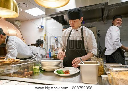 BUSAN, SOUTH KOREA - MAY 28, 2017: staff in modern open kitchen of The Place Italian bistro at Lotte Department Store