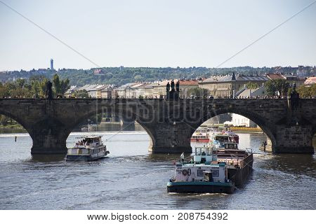 Barge And Tugboat Cargo Ship And River Cruises Sailing In Vltava River Near Charles Bridge