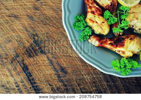 Grilled chicken legs with mustard on plate ..Rustic dinner background . Top view .