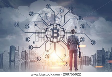 Rear view of a young businessman holding a suitcase looking at a bitcoin network hologram in a morning city sky. Toned image double exposure.